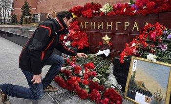 En el Kremlin (Moscú) un hombre se inclina para honrar a las víctimas en una piedra que recuerda a Leningrado, anterior nombre de la ciudad donde ayer sucedió el ataque.