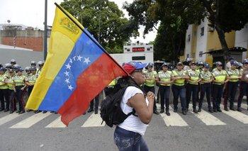 Una manifestante pasa con la bandera de Venezuela frente al cordón policial que dispuso el gobierno.