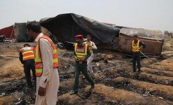 Rescatistas pakistaníes junto al camión cisterna que el domingo explotó en una carretera a casi 700 kilómetros de Islamabad. <br>