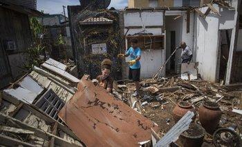Una familia busca restos de muebles entre los escombros que dejó el huracán en su hogar