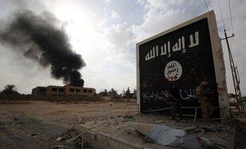 Combatientes iraquíes junto a un muro con la bandera del Estado Islámico