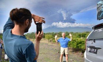 Un turista extranjero se toma una foto con el Agung en actividad detrás suyo, en la isla de Bali, Indonesia. Una erupción puede ser inminente mientras se amplía la zona de exclusión.