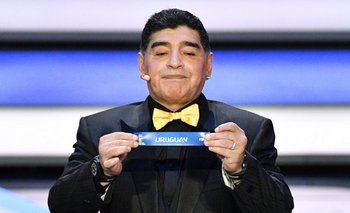 El exfutbolista Diego ArmandoMaradonamuestra la papeleta de Uruguay durante el sorteo del Mundial.