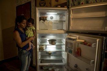 Wuendy Pérez, una madre soltera con cinco hijos, con su hija menor, Wuendy Joselin, junto a su refrigerador casi vacío, en La Guaira. El desabastecimiento afecta a amplios sectores de la sociedad