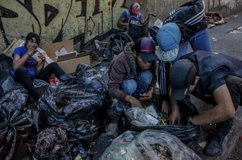 Familias rescatan restos de comida de bolsas de basura