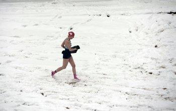 Una mujer corre hacia el agua en la nevada playa de Biarritz, Francia<br>