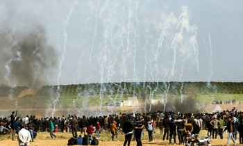 Manifestantes palestinos corren para protegerse del gas lacrimógeno lanzado por las fuerzas de seguridad israelíes