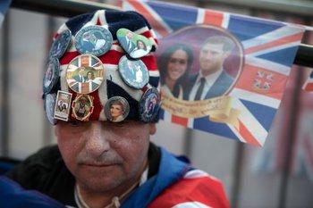Un fanático acampa en las puertas del palacio de Windsor para saludar a los novios el sábado.