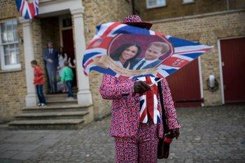Un patriota británico flamea su bandera con la pareja de novios.