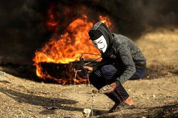 Un palestino con una máscara se enfrenta a las fuerzas israelíes en la Franja de Gaza