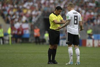 El juez iraní Alireza Faghani presionando al centrocampista alemán Toni Kroos en el partido frente a México el domingo
