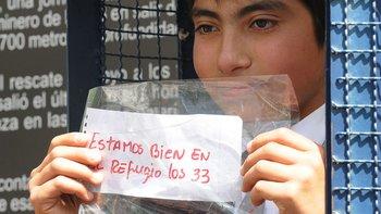 Un estudiante chileno muestra una réplica del célebre mensaje que los mineros colocaron en una sonda para anunciar que estaban vivos.