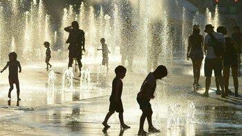 Para combatir el calor, unos niños de Montreal (Canadá) juegan en fuentes de agua.