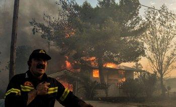 Un bombero llama a sus compañeros ante el avance de las llamas.