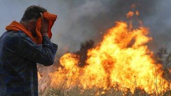 Bomberos y voluntarios intentan extinguir el fuego en el bosque de Penteli.