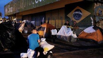 Esta imagen del 8 de agosto muestra a un grupo de venezolanos acampando durante la noche para presentar sus documentos al puesto de control fronterizo de Pacaraima para ingresar a territorio brasileño.