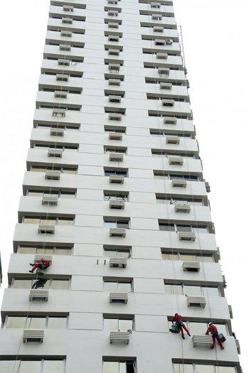 Martes 21. Pintores trabajan con arneses en la fachada del edificio en 18 de Julio y Constituyente.