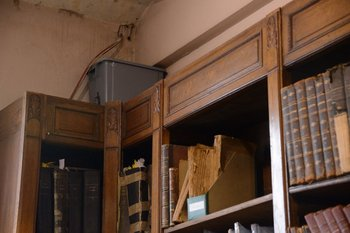 Un balde y una manguera en la biblioteca para escurrir el agua y evitar estropear los libros