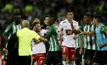 El uruguayo Mario Risso en primer plano no participa; atrás empiezan los incidentes