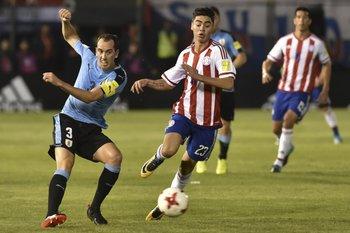 Diego Godín toca la pelota atrás ante la marca de Miguel Almirón