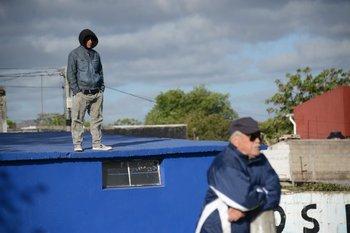 Cacho Blanco siguiendo a Albion y un hincha arriba del techo de los vestuarios<br>