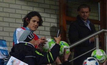 Cavani firmando pelotas y posters con su imagen en PSG<br>