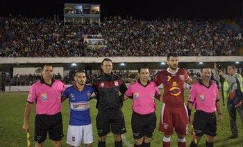 Los capitanes y los árbitros posan delante de la tribuna principal repleta<br>