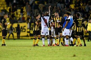 Peñarol-Danubio: Brian Rodríguez, a la izquierda en la foto, observa a distancia el forcejeo entre rivales <br>