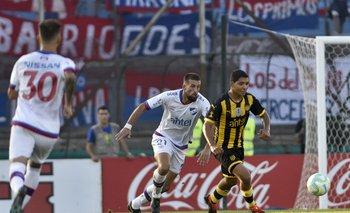 Corujo disputa la pelota con Palacios