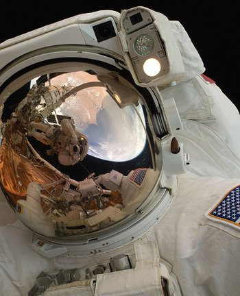 Selfie espacial: el astronauta John Grunsfeld muestra el reflejo de Andrew Feustel desde su traje en plena caminata en el espacio