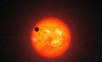 Impresión artística del exoplaneta llamado GJ 1214b, pasando frente a la estrella roja con la que se emparenta
