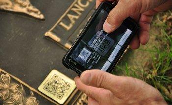Rick Miller, cofundador de Digital Legacys, lee un código QR adherido a una tumba en el Sunset Memorial Park, en Filadelfia